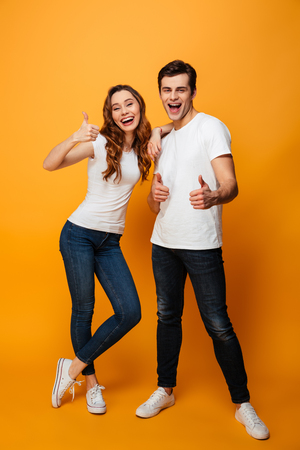 Full length portrait of a cheerful young couple showing thumbs up gesture isolated over yellow background