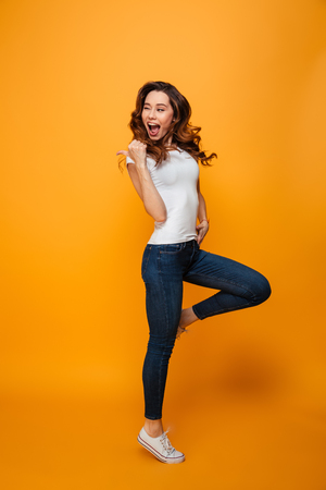 Full length image of Joyful brunette woman in t-shirt jumping and winks while looking and pointing away with thumb over yellow background