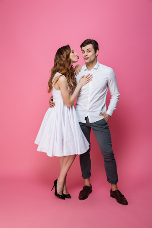 Full length portrait of a young smartly dressed couple posing while standing together isolated over pink background