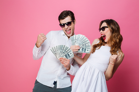 Portrait of a satisfied smartly dressed couple holding bunch of money banknotes and celebrating isolated over pink background