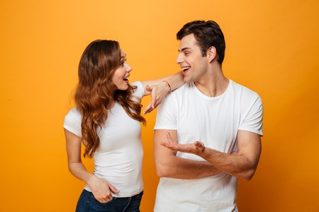 Pleased young lovely couple standing together while talking and looking to each other over yellow background Standard-Bild