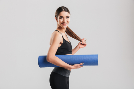 Photo of slim young woman in tracksuit holding yoga mat and looking on camera isolated over gray background