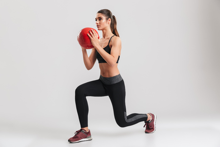 Full-length photo of serious concentrated sportswoman looking aside and doing lunge exercises with fitness ball isolated over gray background