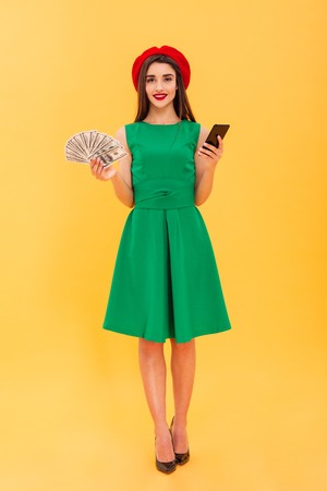 Full length portrait of a smiling young woman dressed in beret and green dress showing bunch of money banknotes and holding mobile phone isolated over yellow background