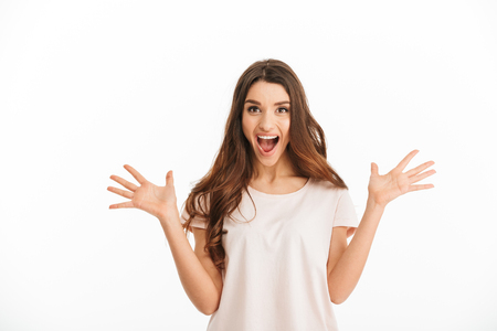 Surprised happy brunette woman in t-shirt screaming and looking at the camera over white background