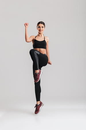Full-length portrait of well-built slim female trainer of instructor in sportswear warming up and doing exercises isolated against gray background Stock Photo