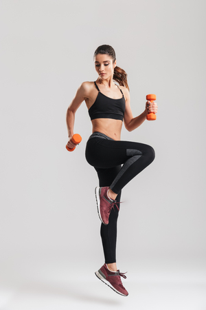 Full-length photo of sporty woman workout with small dumbbells isolated over gray background