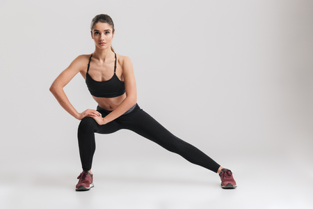 Full-length photo of sporty woman with hair in ponytail stretching her body and doing side lunge exercises isolated over gray background