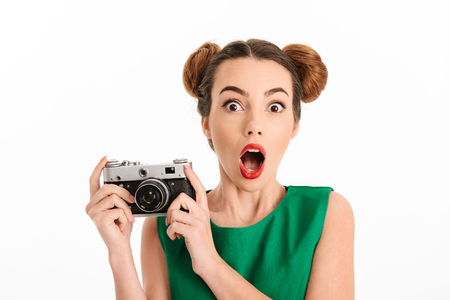 Portrait of a shocked young girl dressed in green dress holding photo camera isolated over white background 写真素材
