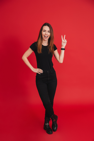 Full-length image of slim woman in total black outfit posing on camera with smile and peace sign isolated over red background 스톡 콘텐츠