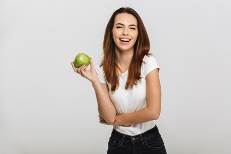 Portrait of a happy young woman holding green apple isolated over white background 免版税图像