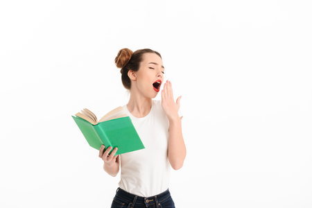 Portrait of a tired casual girl yawning while holding a book isolated over white background