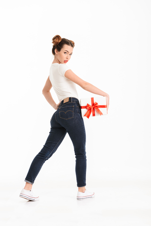 Side view full length portrait of a pretty casual girl holding gift box while looking at camera over her shoulder isolated over white background