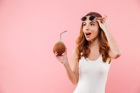 Fascinating brunette woman in swimsuit and sunglasses smiling and looking aside while holding coconut drink in hand, isolated over pink background 스톡 콘텐츠