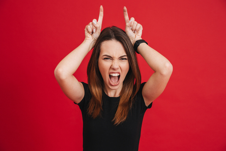 Portrait of crazy woman 20s wearing black screaming and playfully showing horns with two fingers isolated over red background