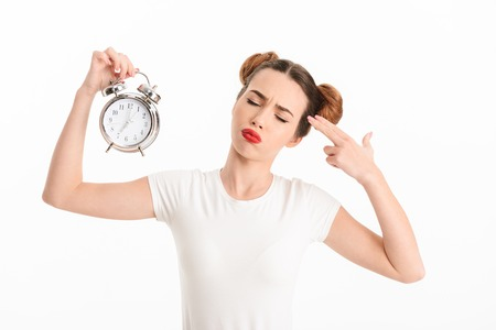 Portrait of an upset casual girl holding alarm clock and showing gun gesture with fingers pointing at her head isolated over white background