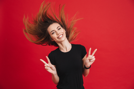 Portrait of a joyful girl showing peace gesture isolated over pink background Reklamní fotografie