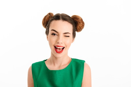 Close up portrait of a beautiful young girl dressed in green dress winking isolated over white background