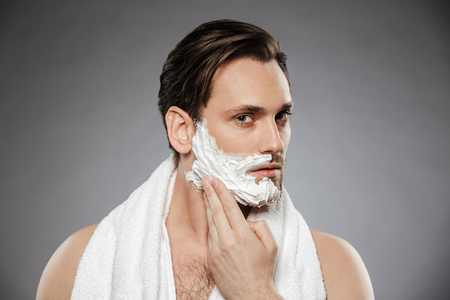 Headshot of concentrated handsome man putting shaving foam on face while having morning skincare isolated over gray backgroung