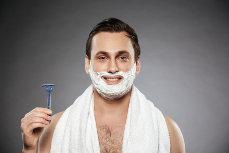 Close up portrait of happy man with shaving foam on his face holding razor isolated over gray background