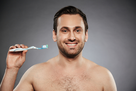 Portrait of a happy shirtless man holding toothbrush with a toothpaste isolated over gray background