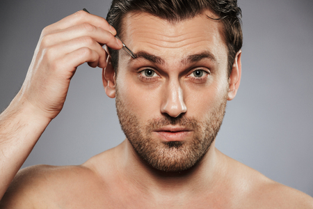 Close up portrait of a confident shirtless man plucking eyebrows with tweezers isolated over gray background