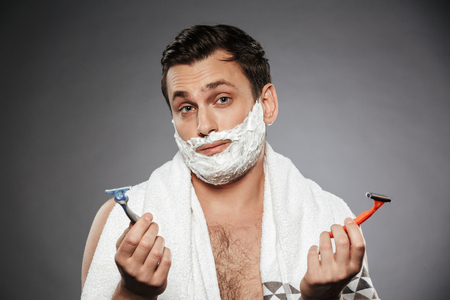 Image of indecisive man with shaving foam on his face holding two razors isolated over gray background