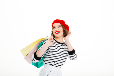 Happy ginger woman with packages corrects her hairstyle and looking away over grey background