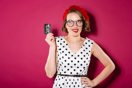 Intrigued ginger woman in dress and eyeglasses with arm on hip holding credit card while bites her lip and looking up over pink background