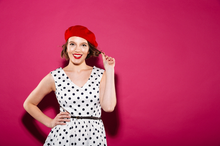 Smiling ginger woman in dress with arm on hip looking at the camera over pink background