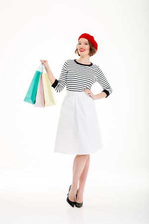 Full length image of Happy ginger woman with arm on hip and packages posing while looking at the camera over grey background Reklamní fotografie