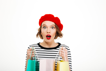 Shocked ginger woman holding packages and looking at the camera over grey background