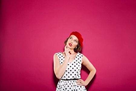 Pensive ginger woman in dress with arm on hip holding her chin and looking up over pink background