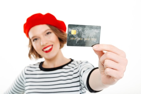 Smiling ginger woman showing credit card at the camera over grey background. Focus on card Reklamní fotografie