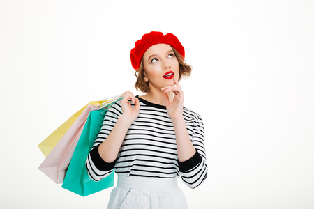 Pensive ginger woman holding packages and looking up while holding her chin over grey background Stock Photo