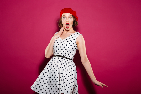 Shocked ginger woman in dress looking at the camera with open mouth over pink background