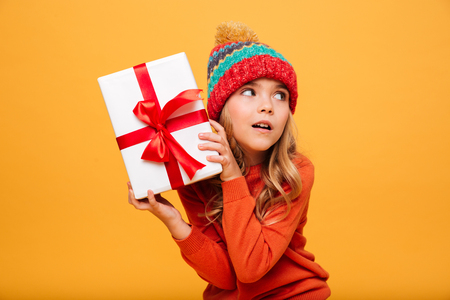 Intrigued Young girl in sweater and hat holding gift box and looking away over orange background