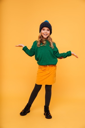 Full length image of Happy Young girl in sweater and hat shrugs her shoulders while looking at the camera over orange background