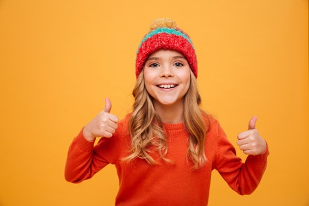 Happy Young girl in sweater and hat showing thumbs up and looking at the camera over orange background