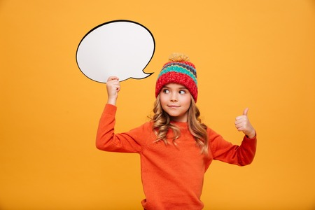 Surprised smiling Young girl in sweater and hat holding blank speech bubble and showing thumb up while looking away over orange background Stock Photo