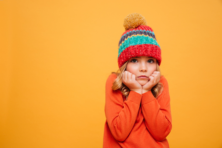 Bored Young girl in sweater and hat reclines on her arms and looking at the camera over orange background Stock Photo