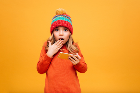 Shocked Young girl in sweater and hat holding smartphone while covering her mouth and looking at the camera over orange background