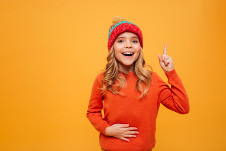Hungry Happy Young girl in sweater and hat holding her tummy and having idea while looking at the camera over orange background 免版税图像