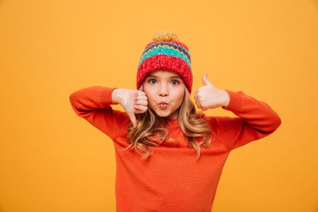 Chica joven divertida en suéter y sombrero mostrando el pulgar hacia arriba y hacia abajo mientras mira a la cámara sobre fondo amarillo Foto de archivo