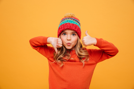 Funny Young girl in sweater and hat showing thumb up and down while looking at the camera over yellow background
