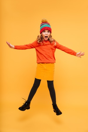 Full length image of Playful shocked Young girl in sweater and hat jumping and looking at the camera over orange background