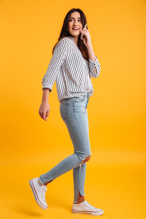 Full length image of happy brunette woman in shirt walking while talking by smartphone and looking away over yellow background