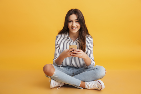 Portrait of a smiling young girl holding mobile phone while sitting and looking at camera isolated over yellow background