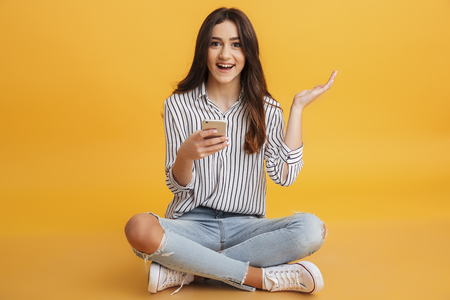 Portrait of an excited young girl holding mobile phone while sitting and looking at camera isolated over yellow background