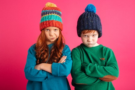 Photo of two displeased angry little children isolated over pink background wearing warm hats. Looking camera. 免版税图像